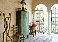 Antique wooden cupboard between traditional farm chairs in an arcade with decorative iron gate