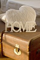 White-painted wooden letters and cushions on old trunk