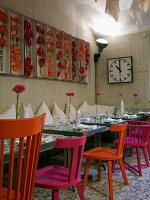 Small tables with colourful chairs, flamingo flowers decorating wall and station clock in restaurant