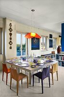 Place settings on modern dining table below pendant lamp with red lampshade in open-plan interior