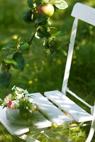 Small bowl of flowers on garden chair