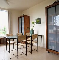 Modern glass table and chairs between two cupboards in dining room