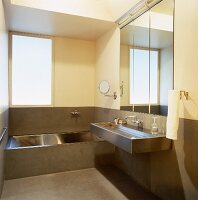 Stainless steel designer bathtub and washbasin against half-height concrete wall panelling