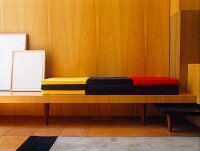 Coloured cushions on bench against wood-panelled wall