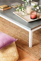Lilac scatter cushion on pale floor cushion next to modern coffee table on sisal rug