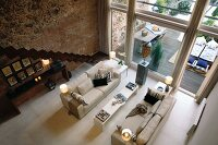 View from above of a sofa landscape in a spacious living room with a bank of windows and natural stone and brick wall