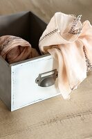 Apricot-coloured cloth in pale grey vintage wooden box