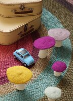Decorative felt mushrooms and toy car on rug