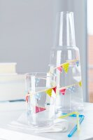 Glass and carafe decorated with tape bunting and matching drinking straws