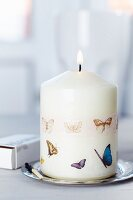 Lit candle decorated with butterfly-patterned tape