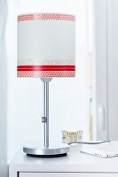 Modern table lamp with lampshade decorated with red patterned tape
