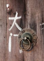 Chinese characters next to metal doorknocker on wooden door