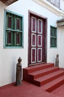 Traditional statues flanking red-painted steps leading to painted front door of house