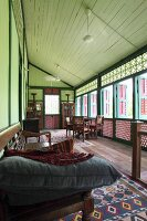 Veranda of traditional Oriental wooden house with latticed wood balustrade and cushions on dark wood bench