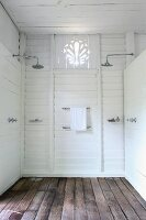Twin shower heads in simple shower area with white wood panelling and wooden floor