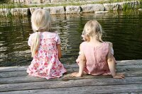 Two blonde girls sitting next to a garden pond