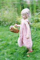 Blonde girl running through garden with basket of flowers