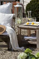 Tray of cut lemons and carafe of water on wooden table next to deckchair