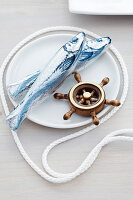 Chocolate fish and miniature ship's wheel on plate with cord