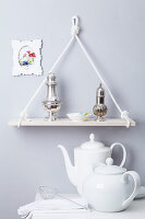 Shelf made of plank and rope hanging above teapot and coffee pot on table