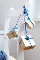 Small parcels tied with cord hanging from back of chair