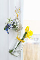 Suspended jar and glass espresso cup holding freesias and forget-me-nots