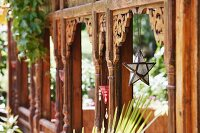 Three-dimensional star hanging from carved wooden panel