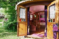 View from garden into circus caravan through open doors: wood-panelled interior with pink-painted ceiling and pink armchair