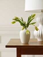 White Vase of Flowers on a Table with a White Lamp