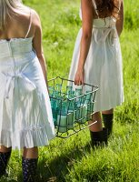 Girls in nostalgic summer dresses carrying several milk bottles in metal crate