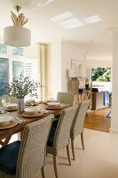 Festively set oak table with modern wicker chairs in open-plan living-dining room