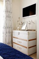 White steamer trunk as maritime chest of drawers in bedroom with blue, quilted bedspread in foreground