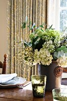 Bouquet in subdued colours in glazed ceramic vase and glasses with embossed pattern on rustic, set wooden table with floral curtain in background