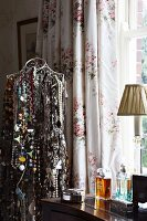 Wire tailor's dummy hung with innumerable necklaces next to antique dressing table with perfume bottles in front of floral curtains at window