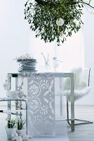 Stacked plates and runner on modern table below mistletoe hanging from ceiling