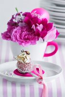 A chocolate on a teaspoon on a saucer, in front of a cup holding pink flowers and a name badge