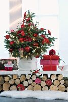 Christmas tree decorated with red baubles and presents on white shelf resting on stacked logs