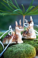 Two deer figurines on bed of moss gazing adoringly at one another