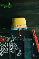 Honey yellow lampshade decorated with applied flowers and pompom trim next to colourful crochet blanket and fake zebra-skin blanket