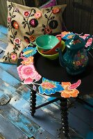 Floral coffee pot on side table with floral motif and cushion with crocheted floral appliqué