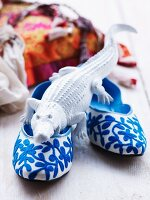 Crocodile ornament on blue and white slippers with floral embroidered pattern