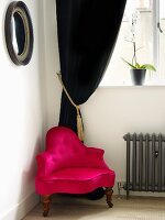 Pink armchair in from of a black, velvet curtain in the corner of a room