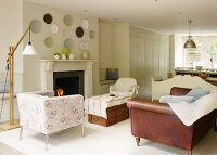 Armchair with floral upholstery and brown leather couch in front of open fireplace in open-plan, country-style interior