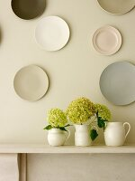 White jugs of hydrangeas on mantelpiece below collection of wall plates
