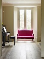 View through open door of red couch in rustic atmosphere in front of French windows with view of garden