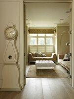 Swedish longcase clock next to open door with view of sofa set below window in rustic interior with pale colour scheme