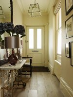 Table lamp and vase of silk flowers on vintage console table in narrow hallway of country house
