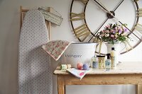 Laundry utensils on rustic wooden table below vintage wall clock