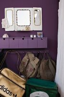 Purple, wall-mounted drawer unit and bags and backpacks hanging from coat rack on purple wall