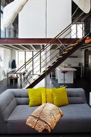 Hanging art object in front of a gray designer sofa with yellow pillows in a loft like living room